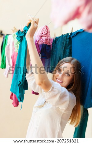 Long-haired housewife drying clothes on clothes-line