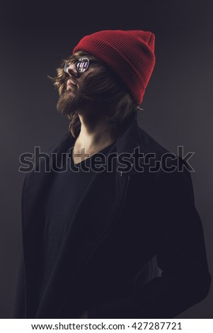 long-haired man with beard and mustache wearing red knitted cap posing over grey background - stock photo