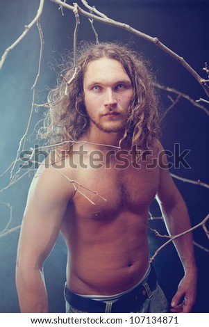 Long haired naked man with scary eyes in the forest, Halloween theme - stock photo