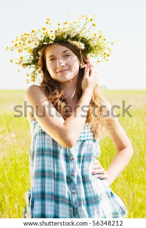 long-haired teen girl  in camomiles chaplet against summer field - stock photo