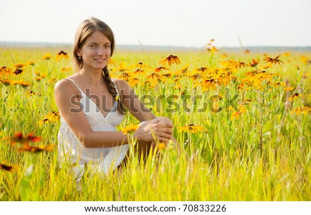 long-haired teen girl is sitting on flowers meadow - stock photo