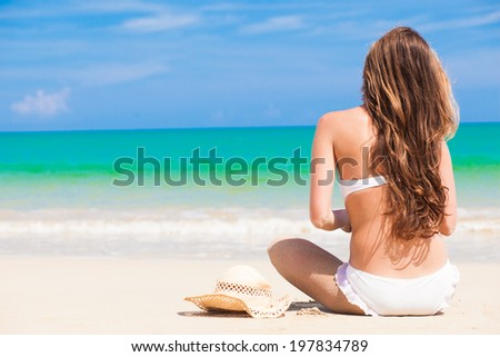 long haired woman in bikini, straw hat and sunglasses at tropical beach - stock photo