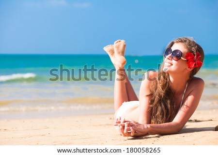 long haired woman in bikini with flower in hair on tropical beach