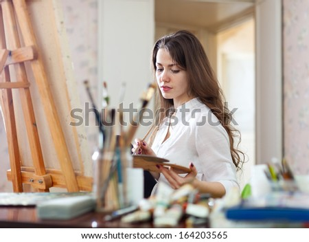 Long-haired woman   paints on canvas in workshop interior - stock photo