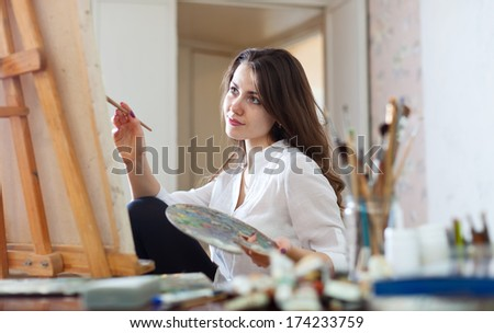 Long-haired woman paints picture on canvas in her studio - stock photo