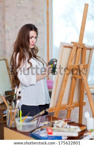 Long-haired woman paints with oil colors on easel in interior - stock photo
