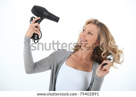 Long haired woman using a hairdryer and large round brush - stock photo