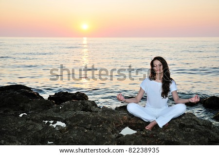 long-haired young woman sitting near the sea and relaxing - stock photo