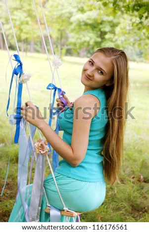 Long-haired young woman swinging on a swing - stock photo