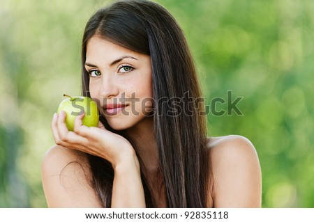 long-haired young woman with bare shoulders holding green apple background summer green park - stock photo