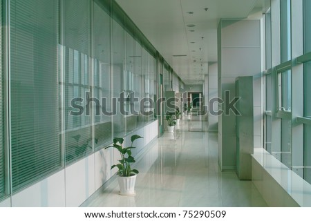 Long hallway in the modern office building with windows - stock photo