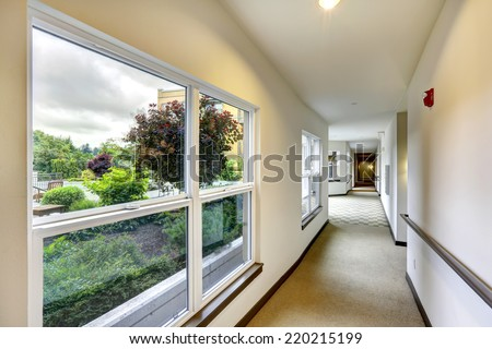 Long hallway with carpet floor and windows in modern residential building.
