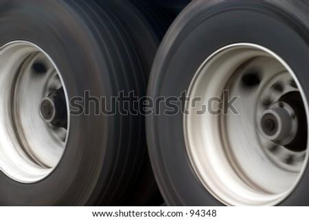 Long haul truck wheels in motion. - stock photo