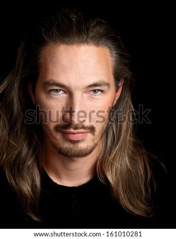 Long hired young smart Oriental man portrait on black background - stock photo