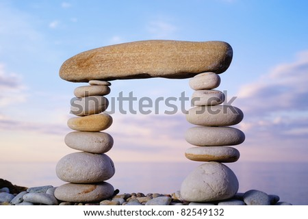 Long horizontal stone is between a pebble piles - stock photo