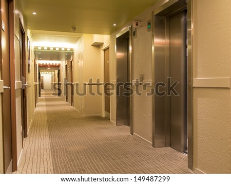 long hotel corridor with doors and elevator - stock photo