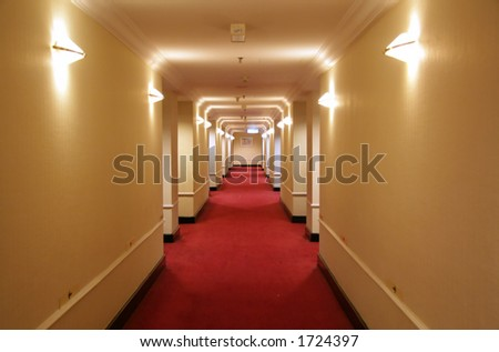 Long hotel corridor with red carpet and yellow wallpaper - stock photo