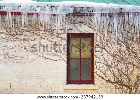 Long icicles hanging from old building roof - stock photo