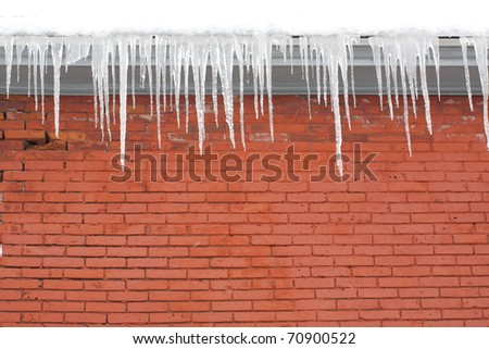 Long Icicles Hanging from Roof down to Red Brick Wall - stock photo