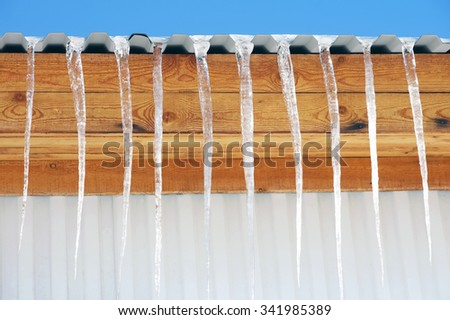 Long icicles hanging from the roof of the house - stock photo