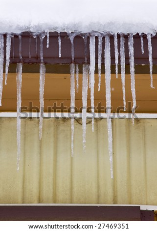 Long icicles hanging off the edge of a barn. - stock photo