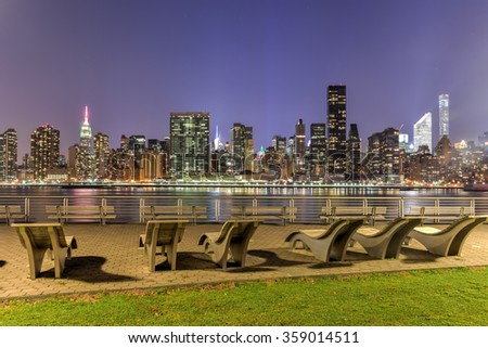 Long Island City, New York - January 2, 2016: Benches along Gantry Park with the New York City skyline view in the background. - stock photo