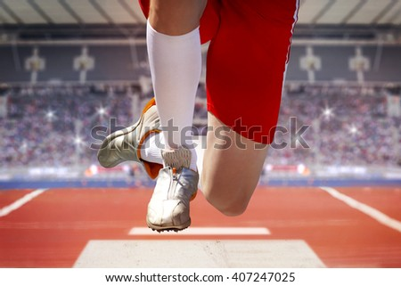 Long jumper in a stadium jumps into the sand box. The background shows fully occupied spectator terraces with sparkling flashlights. - stock photo
