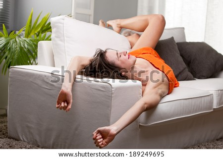 long legs girl yawning and stretching on her sofa while she wakes up - stock photo