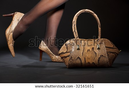 long legs in snakeskin shoes with handbag over black - stock photo