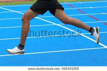 long legs of fast runner runs into the in athletics track