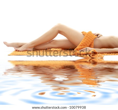 long legs of relaxed lady with orange towel on white sand - stock photo