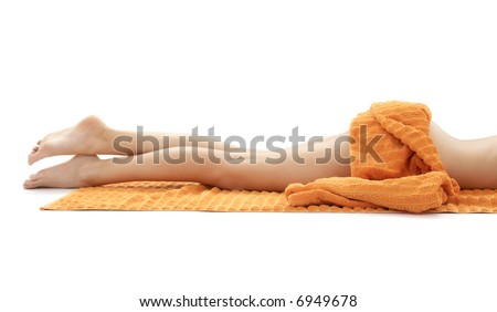 long legs of relaxed lady with orange towel over white - stock photo