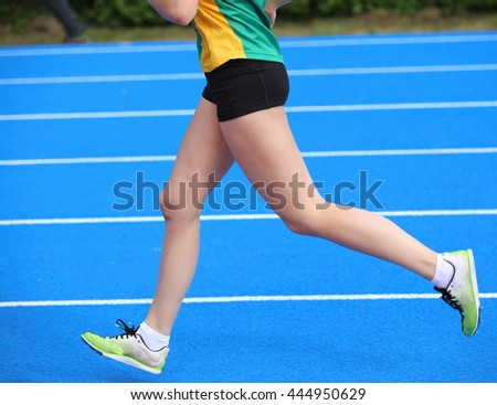 long legs of young female athlete runs in athletics track
