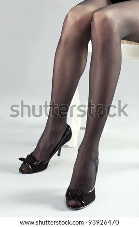 Long legs of young woman wearing black stockings and high-heeled shoes - stock photo
