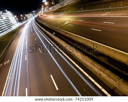 Long light trails from cars on a modern freeway - stock photo