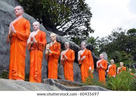 Long line of monks in orange robas in Dambulla, Sri Lanka - stock photo