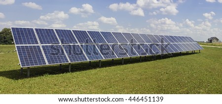 Long line of no name solar electric generation panels on rural  meadow near the village. Panoramic collage from several photos