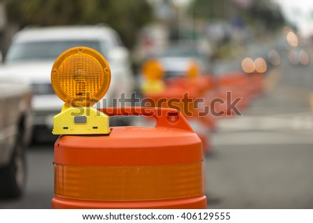 long line of orange traffic barrier barrels to detour traffic around construction zone shallow depth of field - stock photo