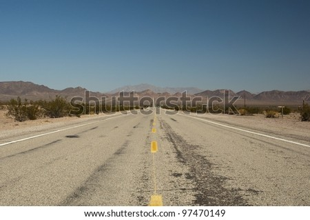 long lonely old asphalt road Route 66 in Arizona and blue sky, lange einsame alte Route 66 im Bundesstaat Arizona mit blauen Himmel - stock photo