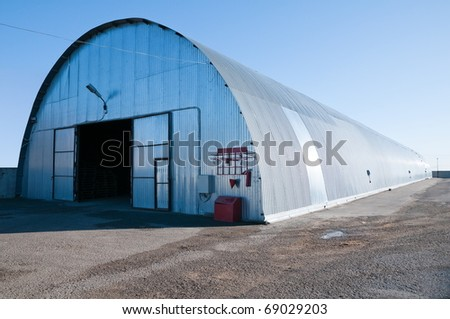 Long metal hangar for goods storage.