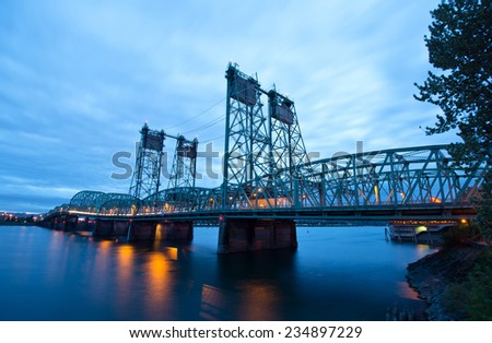 Long metal truss arch bridge with green lifting hoist on high rack in the middle of the Columbia River in the evening with the lights of passing cars on the bridge reflected in the water of river.  - stock photo