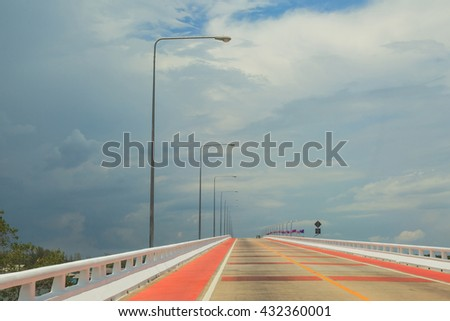Long modern road against blue sky background - stock photo
