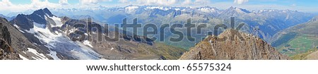 long mountain panorama in summer of the view from Gemsstock mountain above Andermatt in summer seen below in Switzerland with grassy mountains in the front and white mountains behind - stock photo