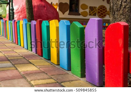 Long multicolour fence in the park