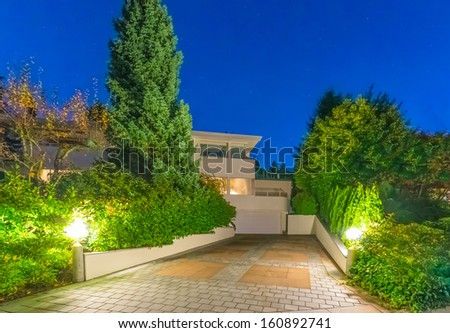 Long nicely paved driveway to garage of the big luxury house at dusk, night time in suburbs of Vancouver, Canada. - stock photo