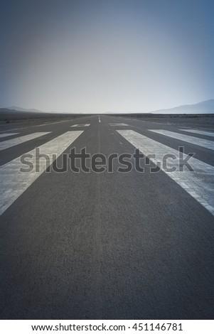 Long paved runway shot from its threshold markings - stock photo
