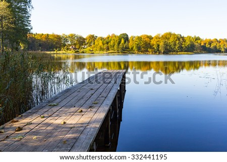 Long pier and a calm lake, with a house far away. - stock photo
