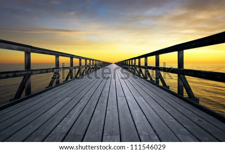 Long pier disappearing into orange sunset - stock photo