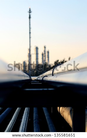 long pipe and silhouette of oil refinery - stock photo