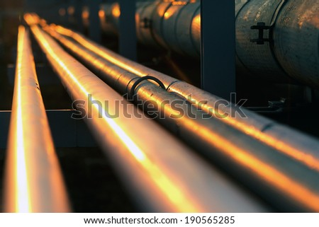 long pipe line in oil refinery during sunset - stock photo